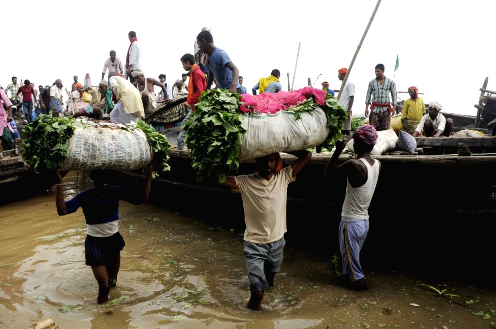 Farmers load their produce on a boat to be taken to the market from the flooded Diara area of Bihar's Danapur after rise in the water levels of Ganga following heavy rains, on Sept 2, 2018.