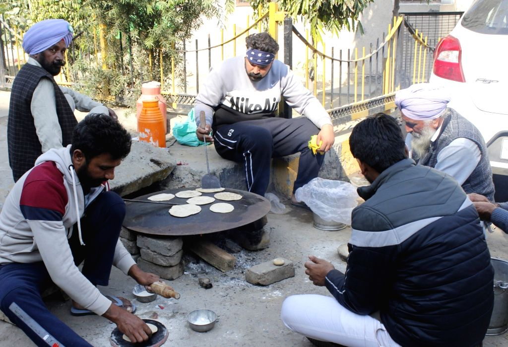 Farmers prepare food during their protest against the Central Government's Farm Laws at Delhi-Haryana's Tikri border, on Nov 28, 2020.