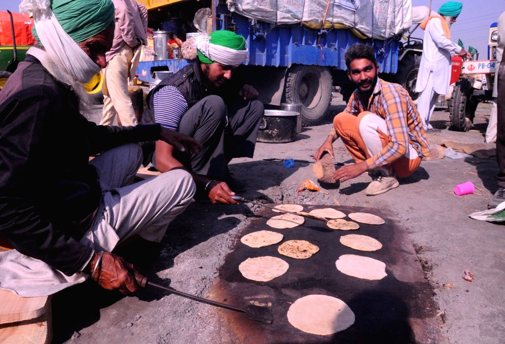 Farmers protesting against the Central Government's agricultural laws prepare food while staging a sit-in demonstration at the Nirankari ground in Delhi's Burari area on Nov 28, 2020.