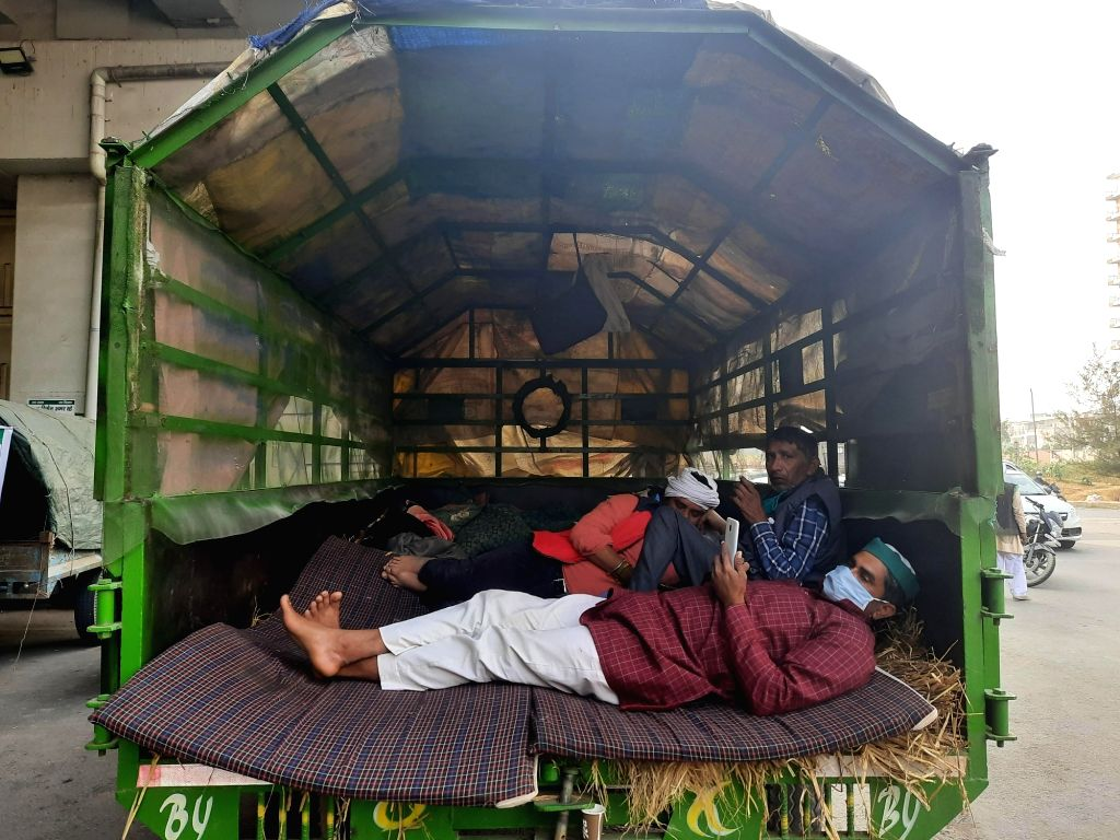 Farmers set up temporary houses in their tractors, sleep on wheat straw