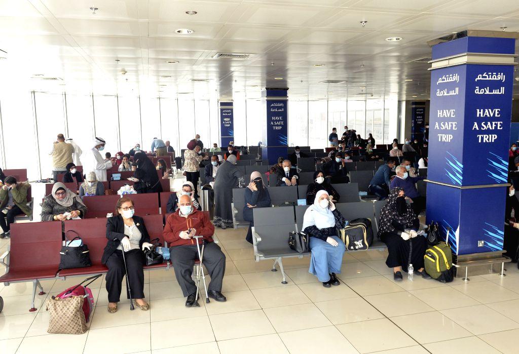 FARWANIYA GOVERNORATE (KUWAIT), March 18, 2020 Egyptian passengers wait for boarding at Kuwait International Airport in Farwaniya Governorate, Kuwait, on March 18, 2020. Kuwait deported ...