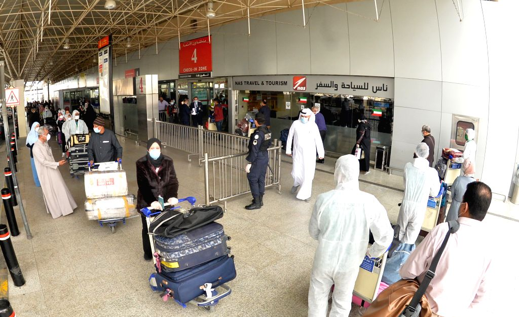 FARWANIYA GOVERNORATE (KUWAIT), March 18, 2020 Egyptian passengers and workers in protective suits are seen at Kuwait International Airport in Farwaniya Governorate, Kuwait, on March 18, ...