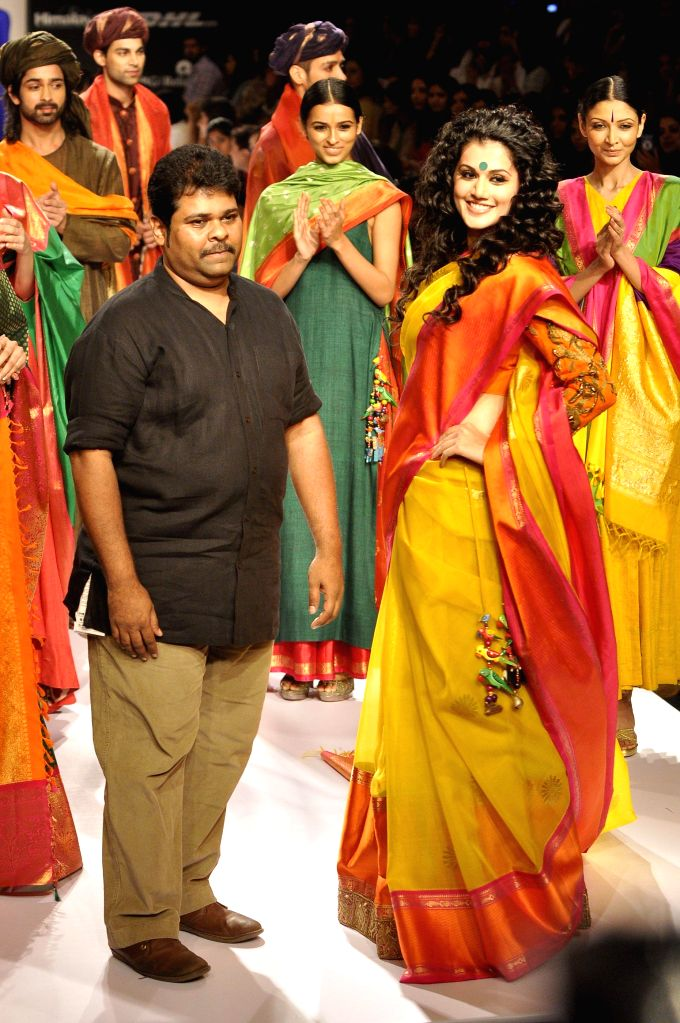 Fashion designer Gaurang Shah walks the ramp with actor Taapsee Pannu during the Lakme Fashion Week (LFW) Winter/ Festive 2014, in Mumbai, on Aug. 22, 2014. - Taapsee Pannu