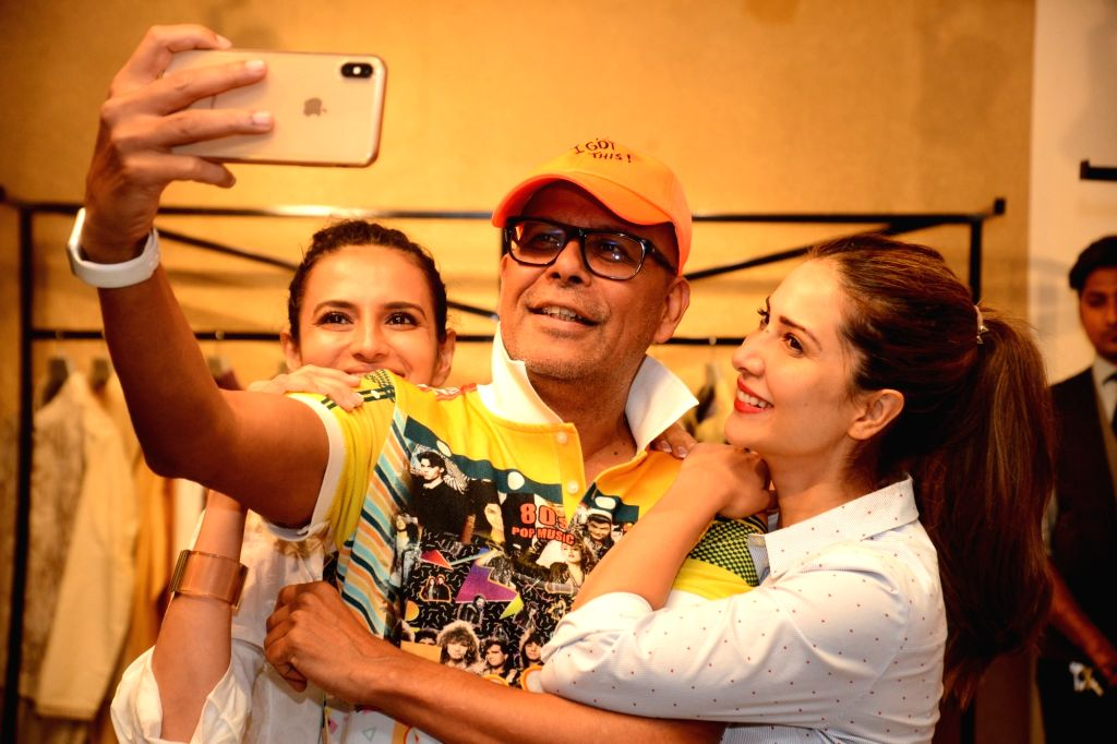 Fashion designer Narendra Kumar poses for selfies at the launch of his store in Mumbai, on May 3, 2019. - Narendra Kumar