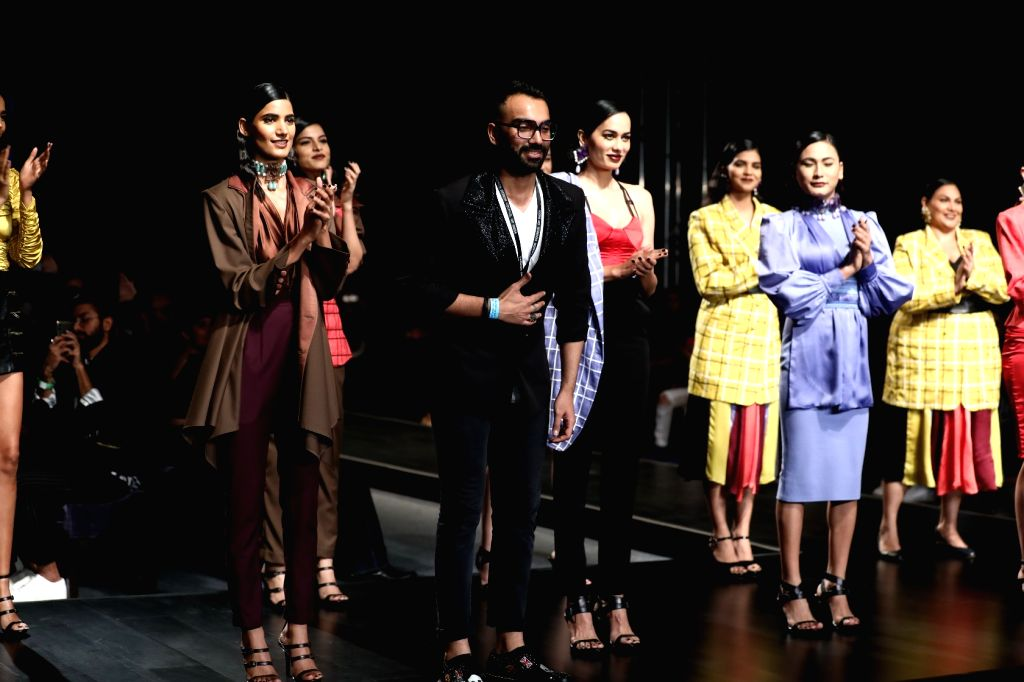 Fashion designer Sameer Madan with models showcasing his creations on the fourth day of Lotus Make-up India Fashion Week, in New Delhi on Oct 12, 2019.