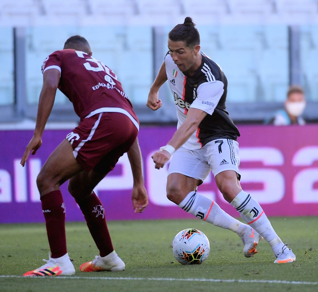 FC Juventus' Cristiano Ronaldo (R) vies with Torino's Bremer during a Serie A football match between FC Juventus and Torino in Turin, Italy, July 4, 2020.