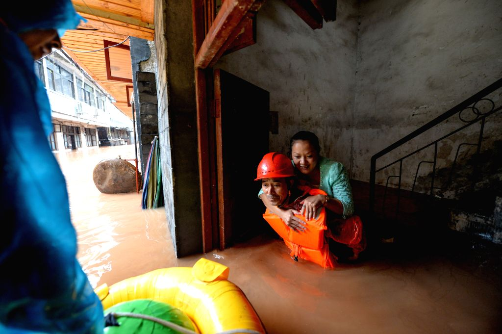 A rescuer helps a woman getting out of a flooded building in the historical town of Fenghuang, central China's Hunan province, July 16, 2014. Continuous rain has .