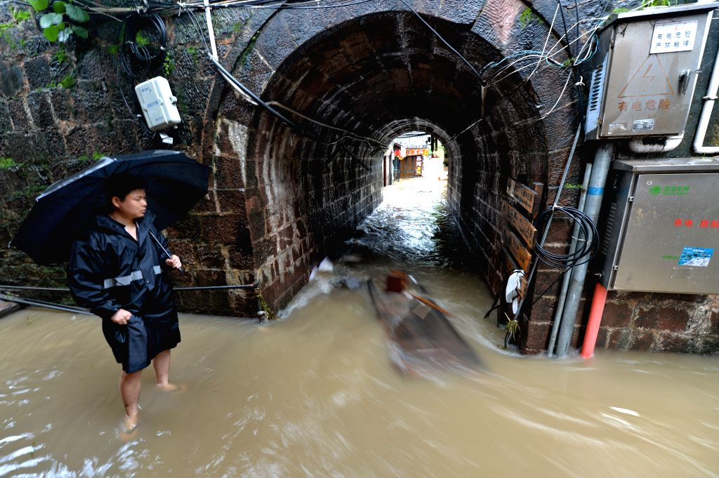 A rescuer stands on a flooded street in the historical town of Fenghuang, central China's Hunan province, July 16, 2014. Continuous rain has flooded the ancient ..
