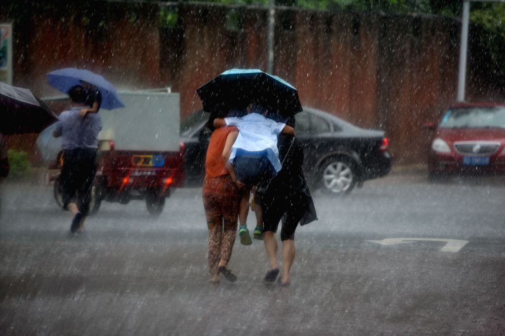 Tourists run in a harsh rain in the historical town of Fenghuang, central China's Hunan province, July 16, 2014. Continuous rain has flooded the ancient town ...