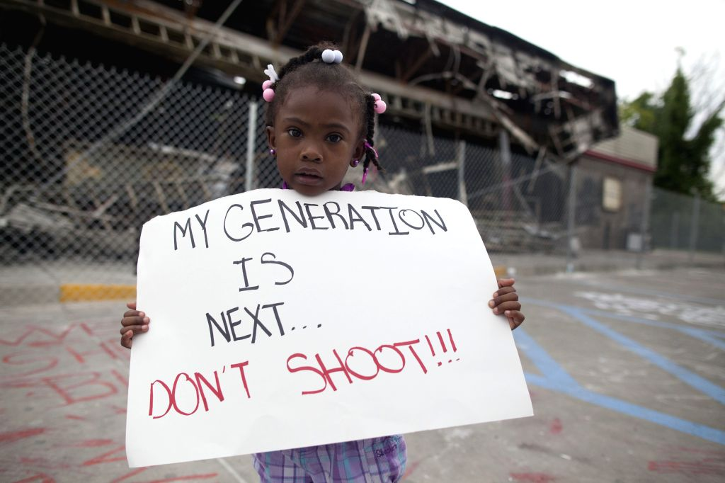 A girl holds a placard during a protest in Ferguson, Missouri, on Aug. 15, 2014. Police in Ferguson in the U.S. state of Missouri, where unrest has erupted since ..