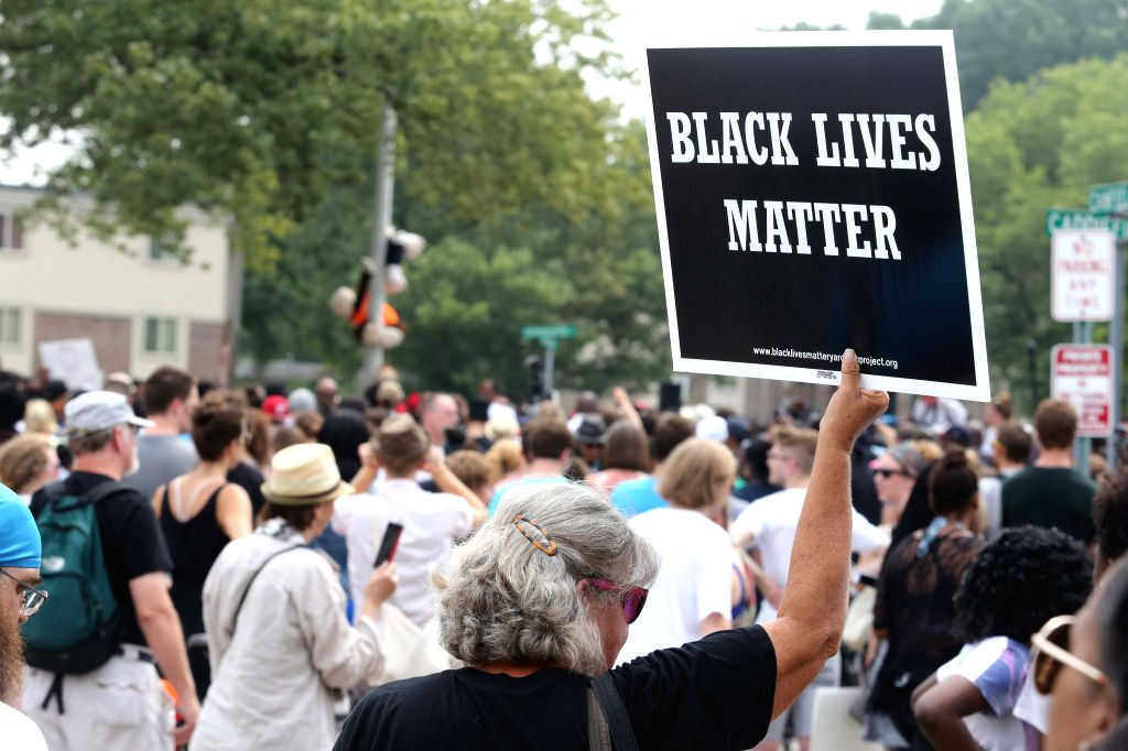 FERGUSON, August 10 A woman holds up a Black Lives Matter sign at the Michael Brown memorial in Ferguson, Missouri, U.S., on August 9, 2015. Several hundred people gathered in Ferguson on ...