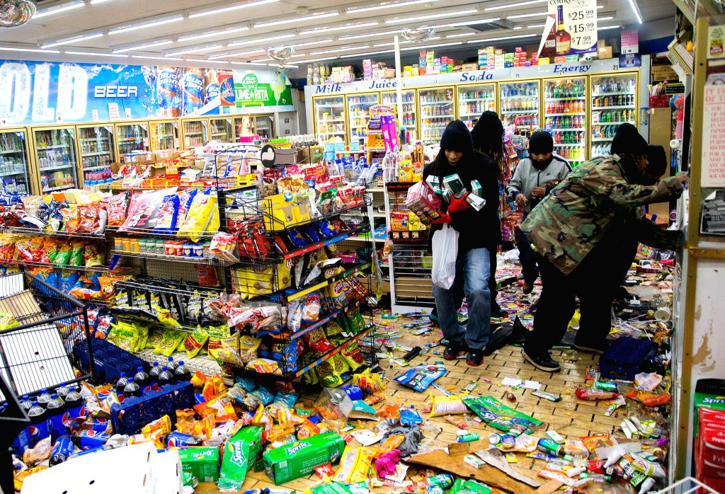 Ferguson (U.S.):   Demonstrators loot a local business in Ferguson, Missouri, the United States on Nov. 24, 2014. Violence erupted Monday night in Ferguson after the announcement that police officer .