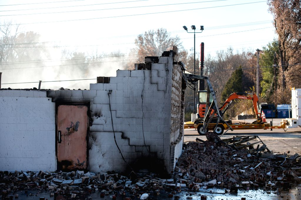 Ferguson (U.S.): Ruins of a local business are seen after being burnt down over night in riot in Ferguson, the U.S., on Nov, 25, 2014. Tens of thousands of people in 90 cities of the U.S. held ...