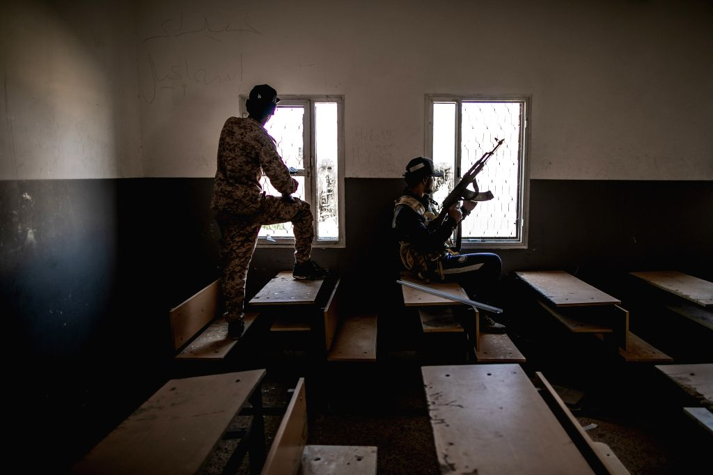 Fighters of the UN-backed Government of National Accord (GNA) take positions at an abandoned school during clashes with East-based Libyan National Army forces at ...