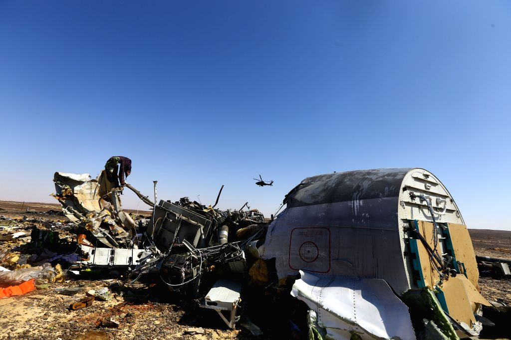 File photo taken on Nov. 1, 2015 shows an Egyptian military helicopter flying over debris of a Russian passenger airplane which crashed at the Hassana area, north ...