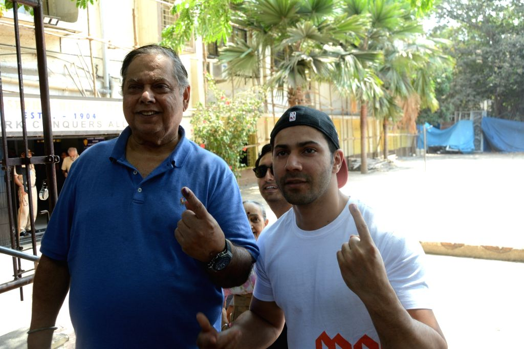 Filmmaker David Dhawan and his son actor Varun Dhawan show their forefingers marked with indelible ink after casting vote during the fourth phase of 2019 Lok Sabha elections in Mumbai on ... - David Dhawan