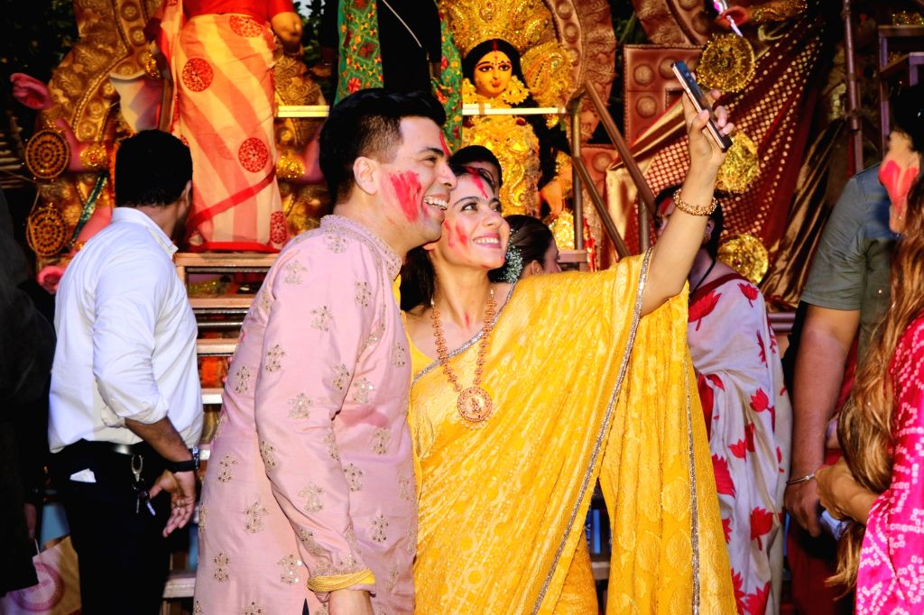 Filmmaker Karan Johar and actress Kajol pose for selfies during Vijaya Dashami celebrations, in Mumbai on Oct 8, 2019. - Karan Johar and Kajol