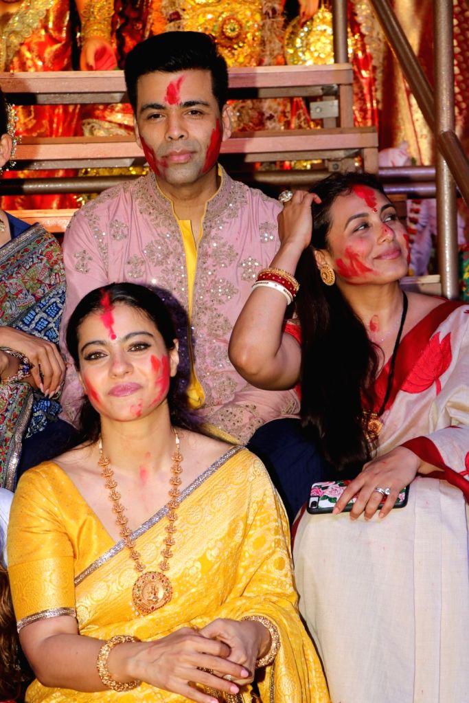 Filmmaker Karan Johar with actors Kajol and Rani Mukerji during Vijaya Dashami celebrations, in Mumbai on Oct 8, 2019. - Karan Johar, Kajol and Rani Mukerji