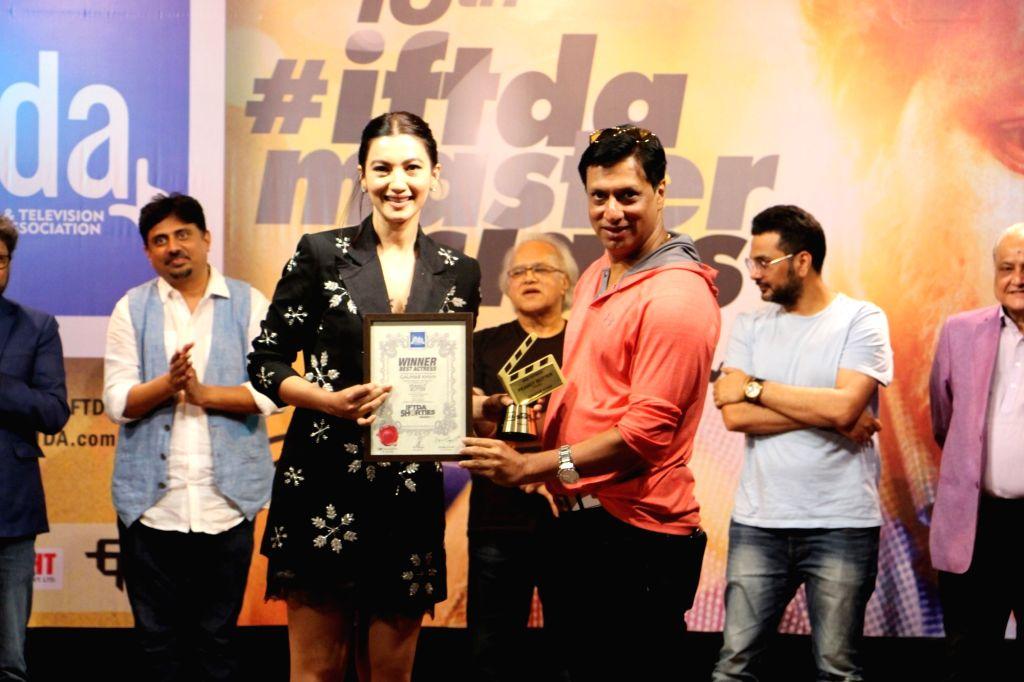 Filmmaker Madhur Bhandarkar felicitates actress Gauhar Khan at a master class organised by Indian Film and Television Directors' Association (IFTDA), in Mumbai on May 19, 2018. - Madhur Bhandarkar and Gauhar Khan