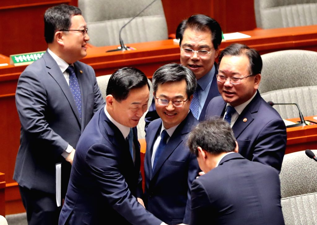 Finance Minister Kim Dong-yeon (C) greets other Cabinet ministers and lawmakers ahead of the National Assembly plenary session in Seoul on May 21, 2018. After more than 40 days of partisan ... - Kim Dong