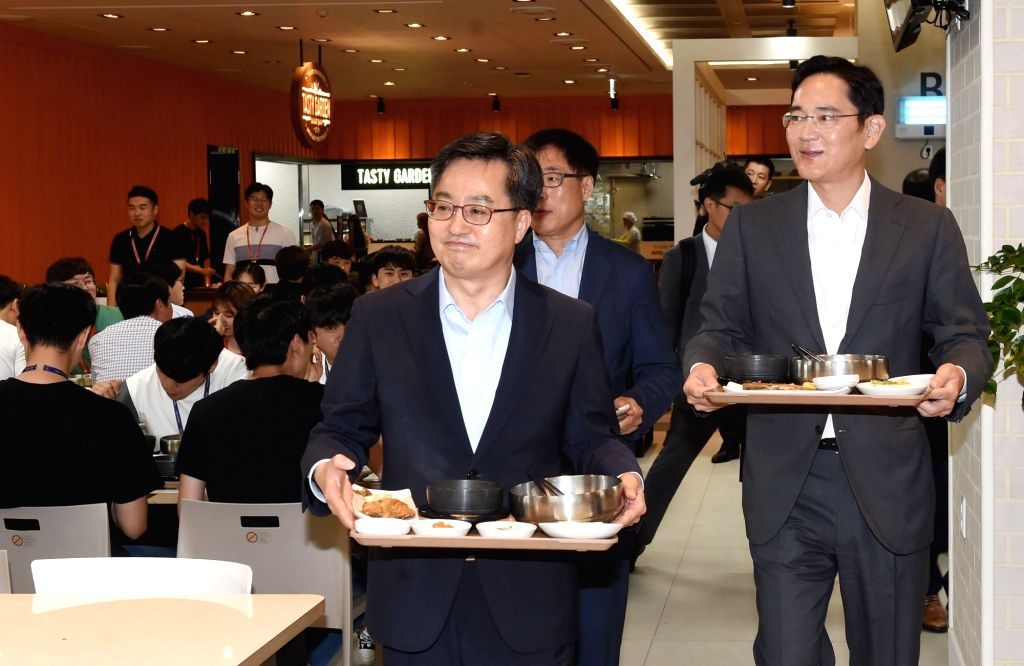 Finance Minister Kim Dong-yeon (L) carries a tray at a restaurant at Samsung Electronics Co.'s factory in Pyeongtaek, Gyeonggi Province, on Aug. 6, 2018, in this photo courtesy of the ... - Kim Dong