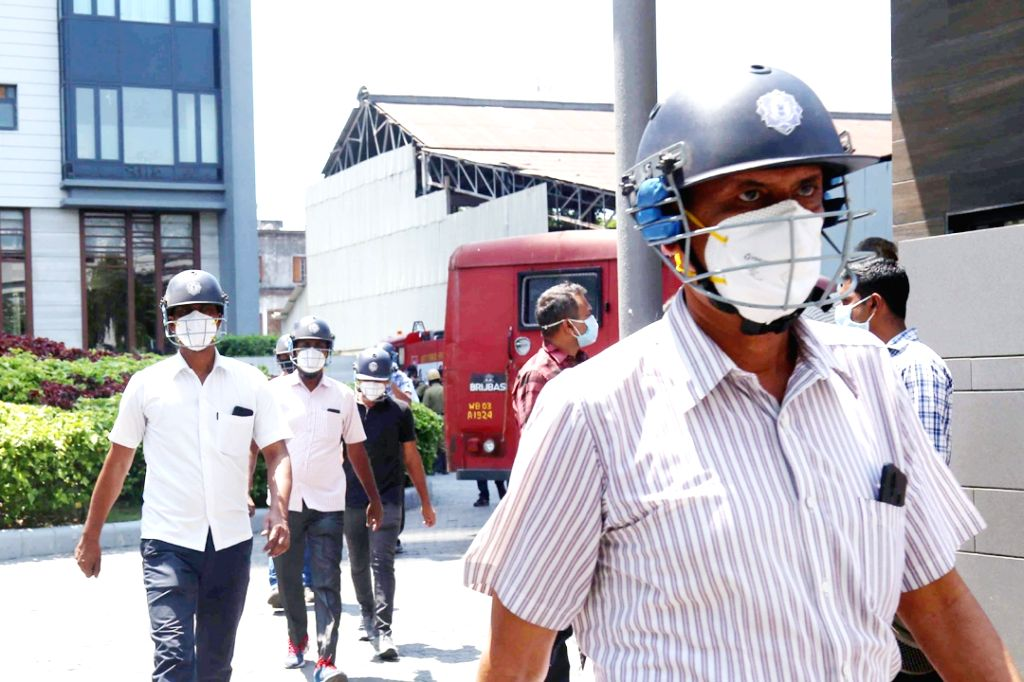 Fire and police personnel arrive wearing masks at a high-rise building, the 16th floor of which caught fire amid lockdown in the wake of COVID-19 pandemic, in Kolkata on March 30, 2020.
