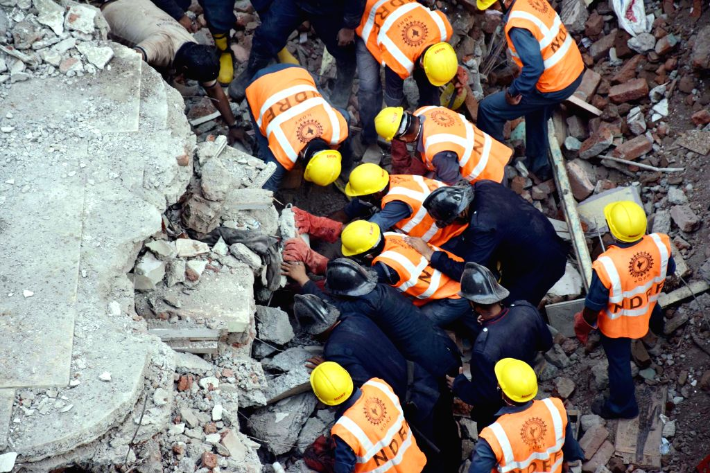 Fire brigade and NDRF personnel carry out rescue operation at the site where a three-storey building collapsed in Thane, Maharashtra, on Aug 4, 2015. Atleast 11 persons died and five people ...