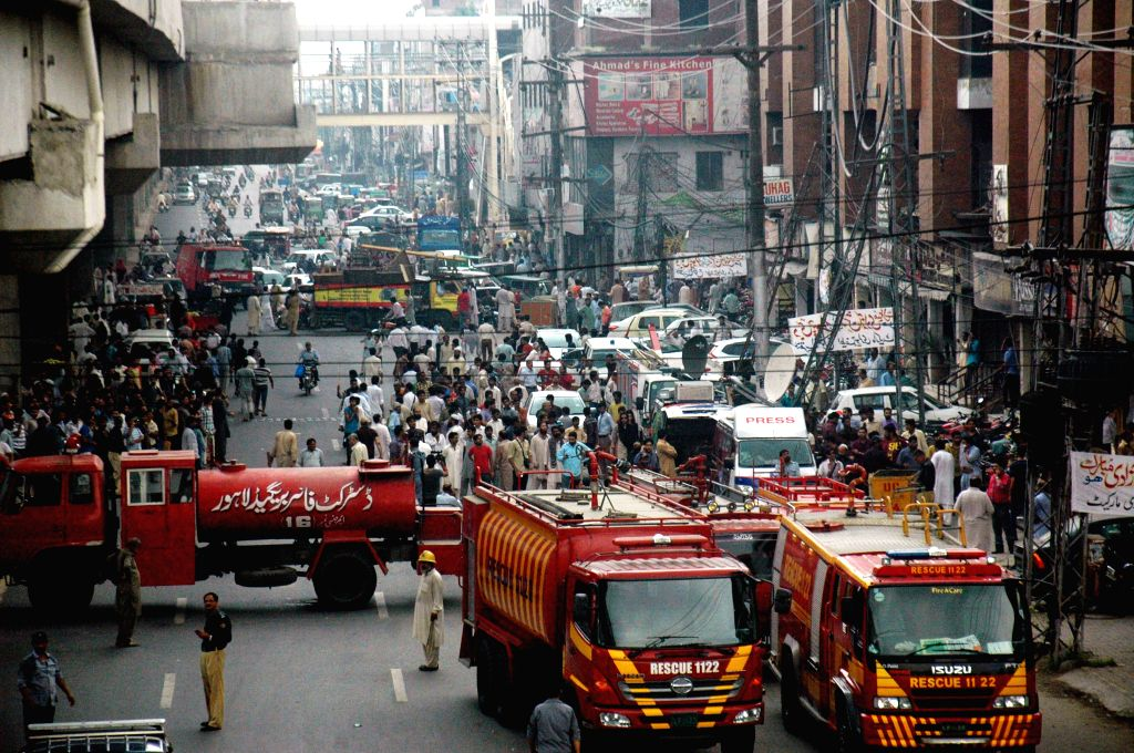 Fire brigades arrive at the fire site in eastern Pakistan's Lahore, Aug. 11, 2015. At least one man was killed while 11 others injured on Tuesday when fire engulfed ...