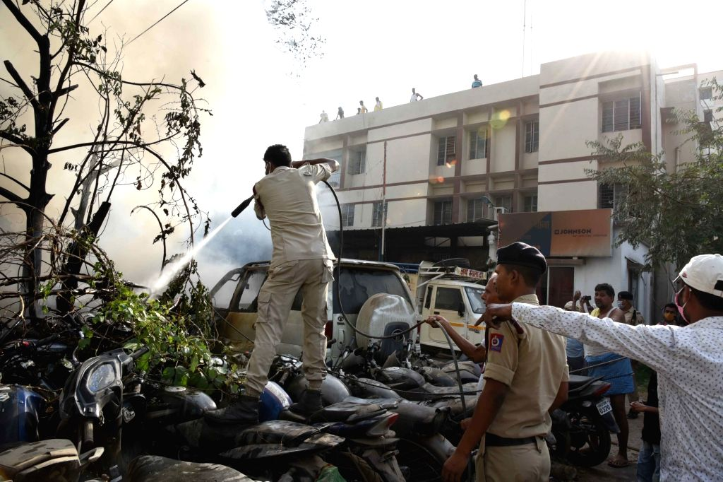 Fire fighter attempts to douse fire broke out from seize vehicles in Agamkuan Police station, in Patna, Friday, April 23, 2021.