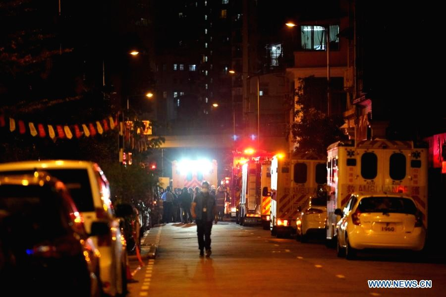 Fire fighters and police officers investigate a fire scene in Hong Kong, Nov 15, 2020.