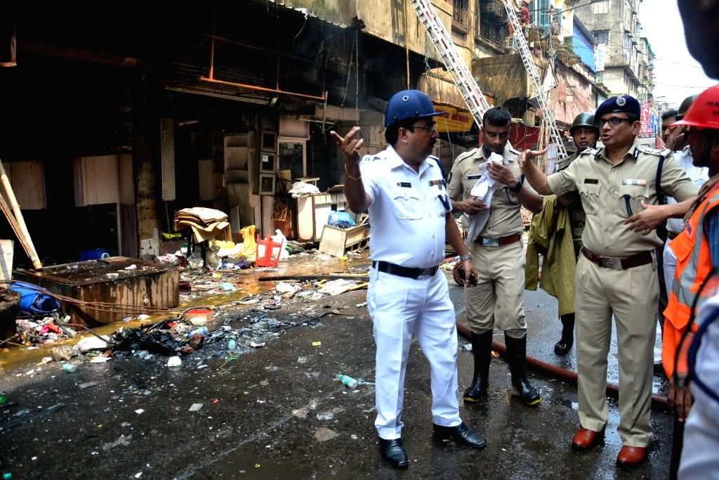 Fire fighters and police personnel during firefighting operations at Bagree market where a fire broke out on Sunday; in Kolkata on Sept 18, 2018.