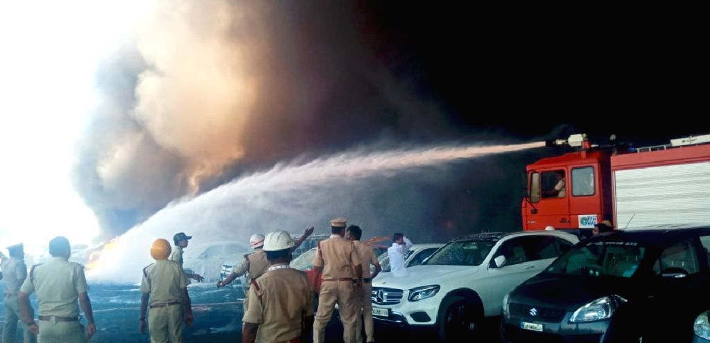 Fire fighters busy dousing a fire that broke out in the parking lot in front of Yelahanka Air Force Station gutting 300 cars, in Bengaluru on Feb 23, 2019. The fire, which began at around ...