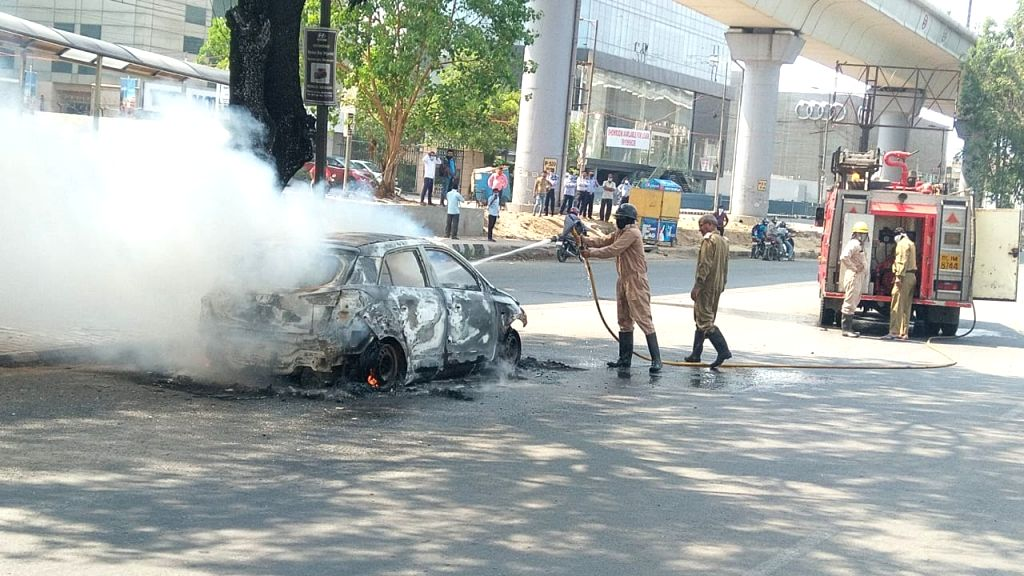 Fire fighters douse fire that broke out inside a car on Mathura Road.