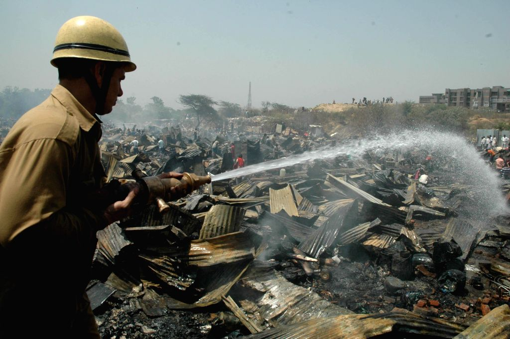 Fire fighters douse the fire which engulfed a slum cluster of south Delhi''s Vasant Kunj gutting around 500 hutments on April 25, 2014.