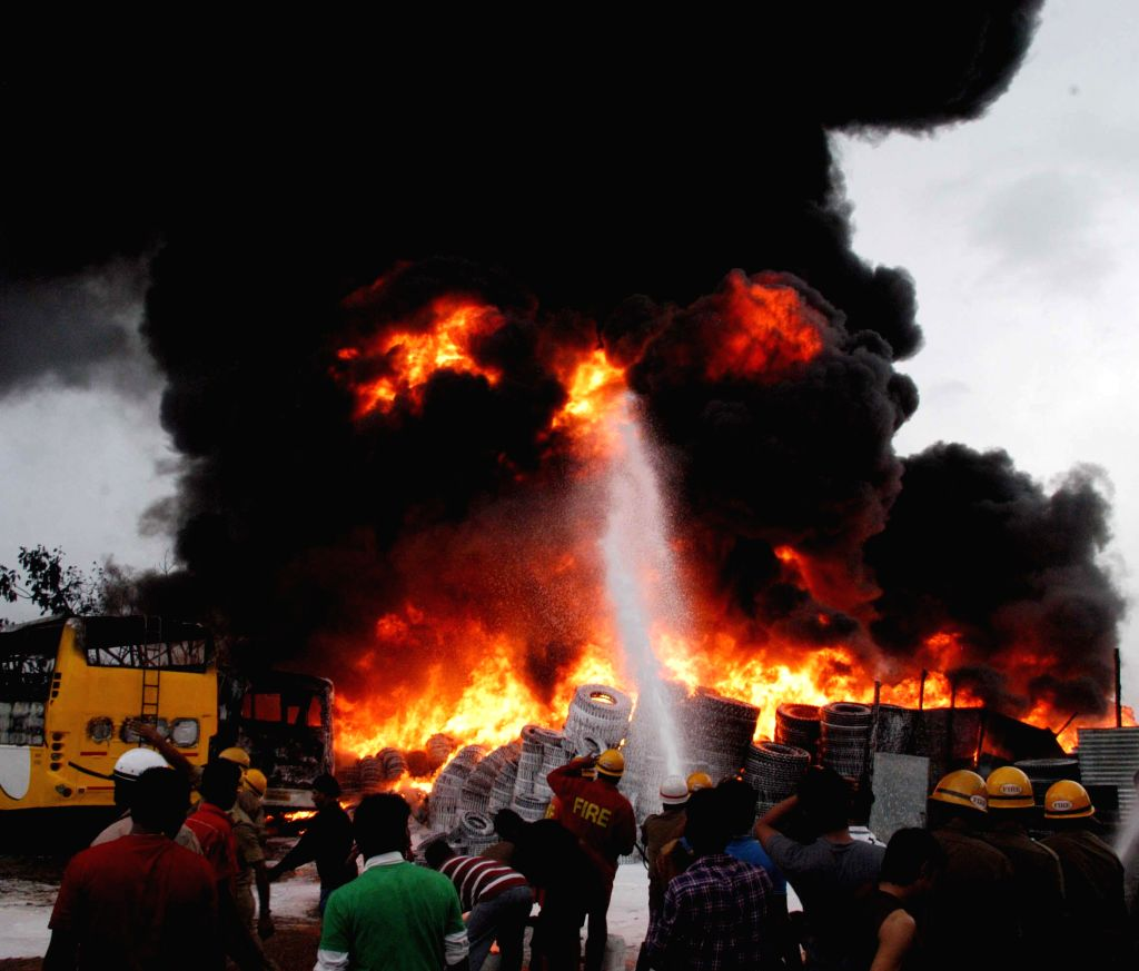Fire fighters try hard to douse a fire that broke out at an old bus depot near TR Mills, Chamrajpet, in Bangalore on Aug 3, 2014.