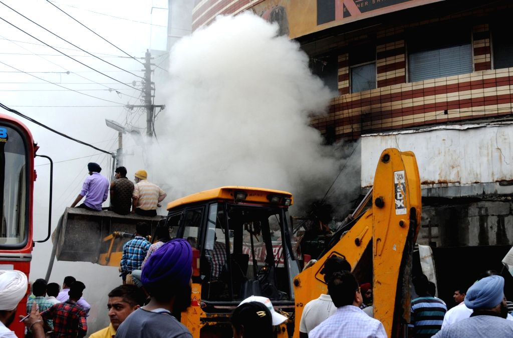 Fire fighters try to douse a fire that broke out at a shoe store in Amritsar on July 4, 2016.
