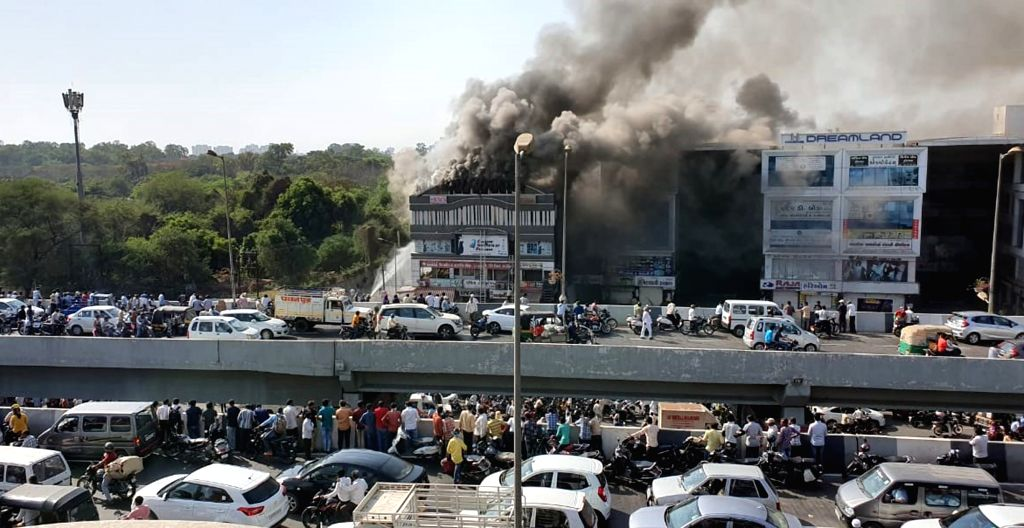 Fire fighting operations underway after a massive fire broke out at a coaching centre atop a four-storey building, in Sarthana area of Gujarat's Surat on May 24, 2019. 17 students were killed ...