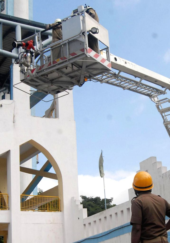 Fire personnel demonstrating during a mock drill of fire personnel at Kanteerava Stadium in Bangalore on Dec. 14, 2013.
