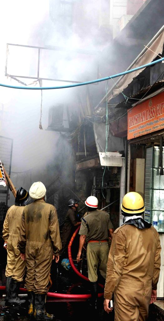 Firefighters busy dousing fire that broke out in Kinari Bazar of old Delhi's Chandni Chowk area - a wholesale retail market specialising in wedding attire and accessories on Aug 25, 2014.