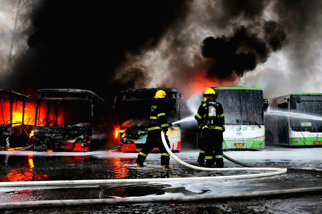 Firefighters work at a bus depot in Huli District of Xiamen City, southeast China's Fujian Province, July 22, 2015. One guard on duty was killed in the fire which ...