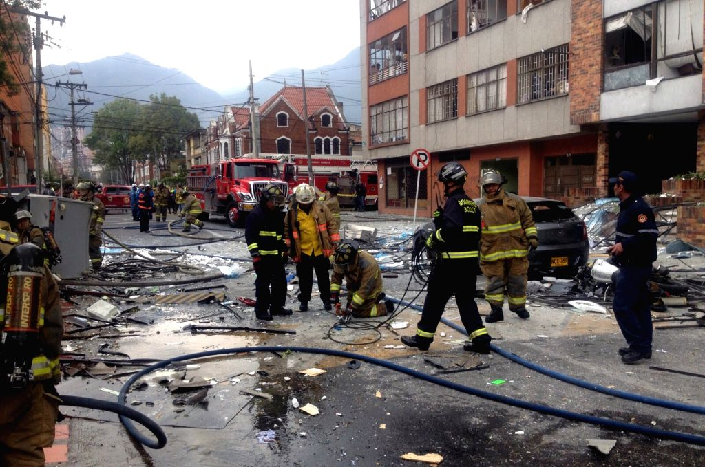 Firefighters work at the explosion site of a pharmaceutical company in Galerias neighborhood, in Bogota, Colombia, on Nov. 2, 2015.