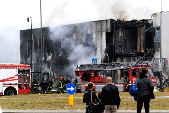 Firefighters work on the site of a plane crash in Milan, Italy, Oct. 3, 2021.