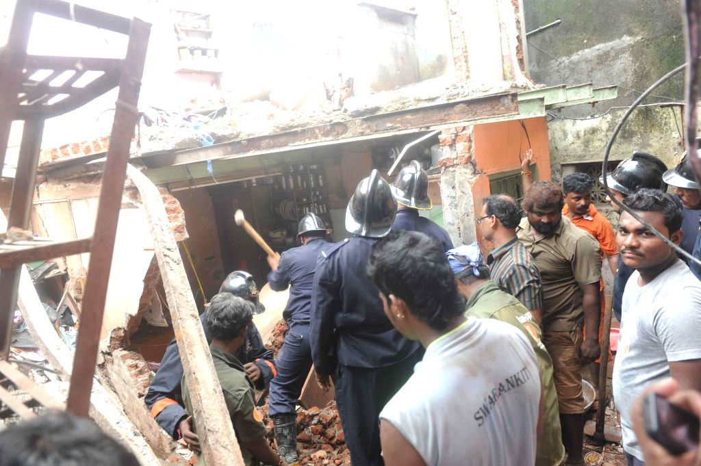 Firemen and BMC officials carry out rescue operations after a cylinder blast in Chembur of Mumbai on Aug 25, 2014. Reportedly at least one person was killed and 10 others injured in the accident.