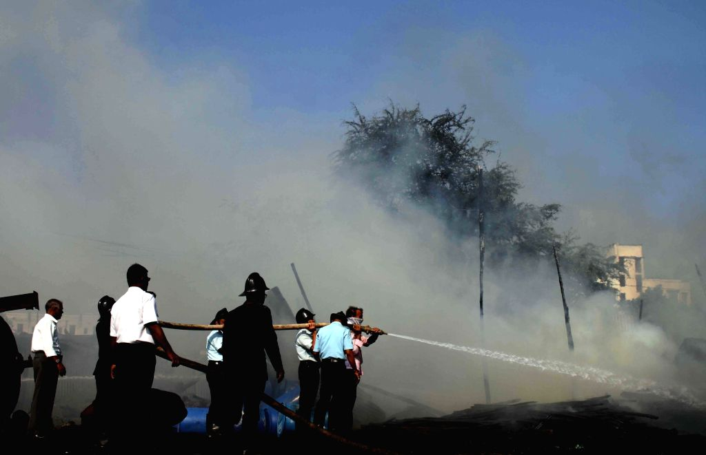 Firemen extinguish a fire which broke out due to chemical boiler tanker blast at Dombivali near Davdi naka in Thane district on on Dec.6, 2013. Four people were killed in the accident. (Photo: B L ...