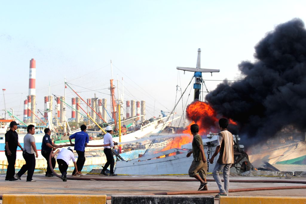 Firemen try to extinguish the fire on a ship carrying 800 tons of fertilizer in Gresik Port, East Java, Indonesia, Aug. 25, 2015. The fire was caused by electricity ...
