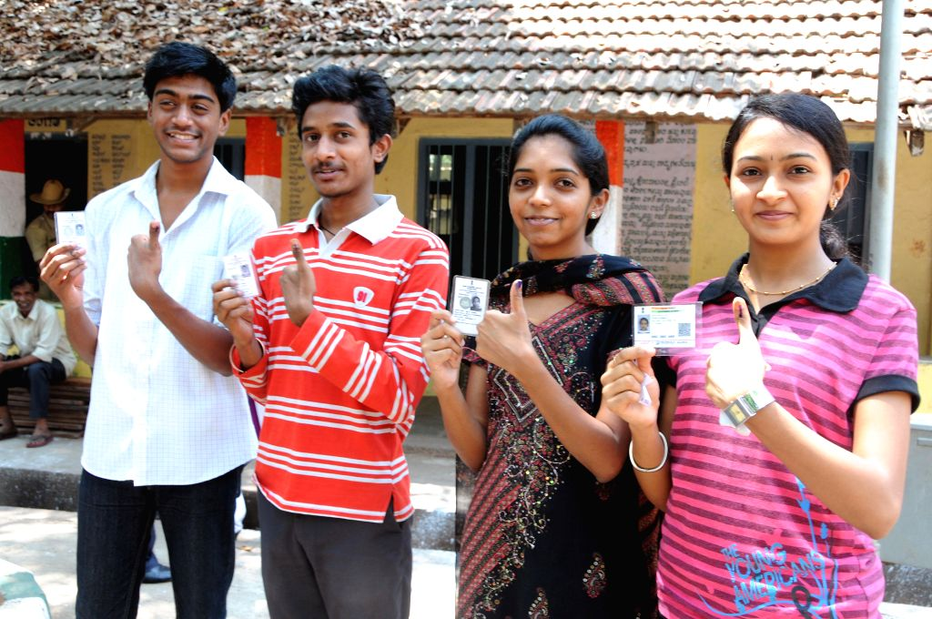 First Time Voters display their inked thumbs and Identification Cards, after casting their vote for Loksabha Elections 2014, in Bangalore on April 17, 2014.