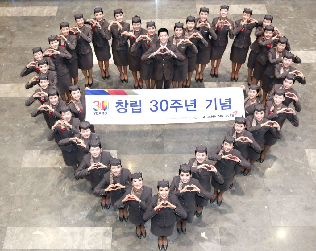 Flight attendants of Asiana Airlines Inc., South Korea's No. 2 carrier, hold a ceremony to mark the airline's 30th anniversary at its office in western Seoul on Feb. 14, 2018, in this photo ...