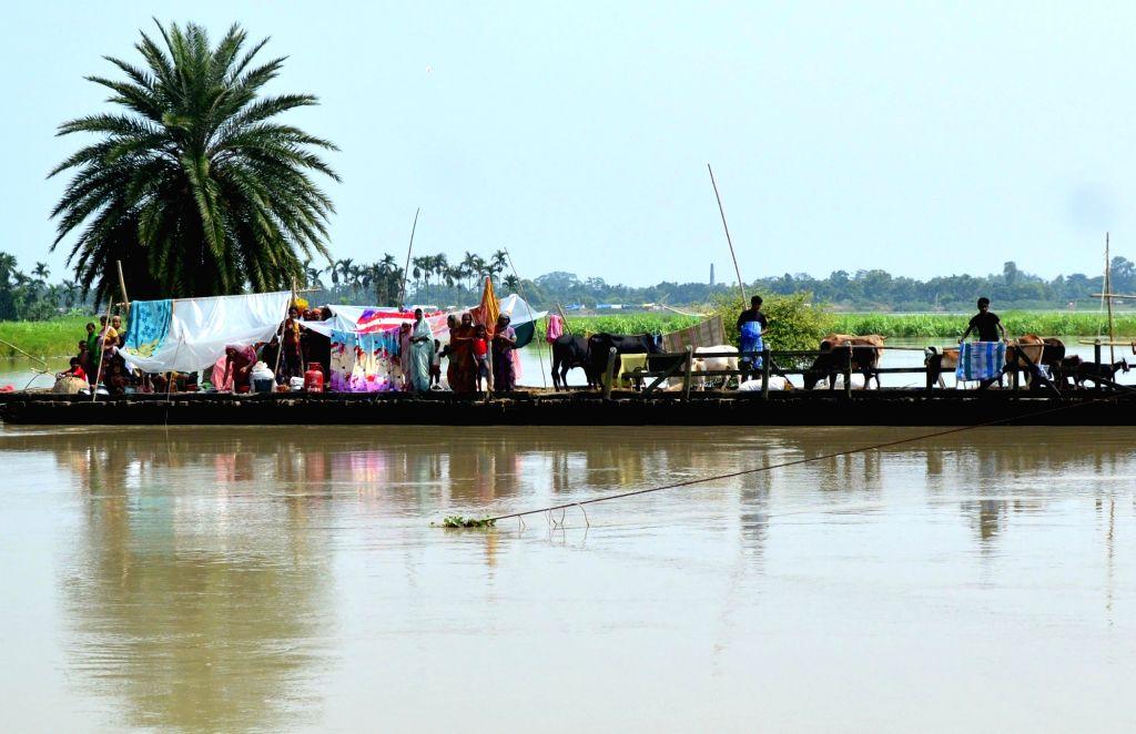 Flood victims take refuge on a wooden bridge built over Mora Kalahi river in Boko of Assam's Kamrup district.