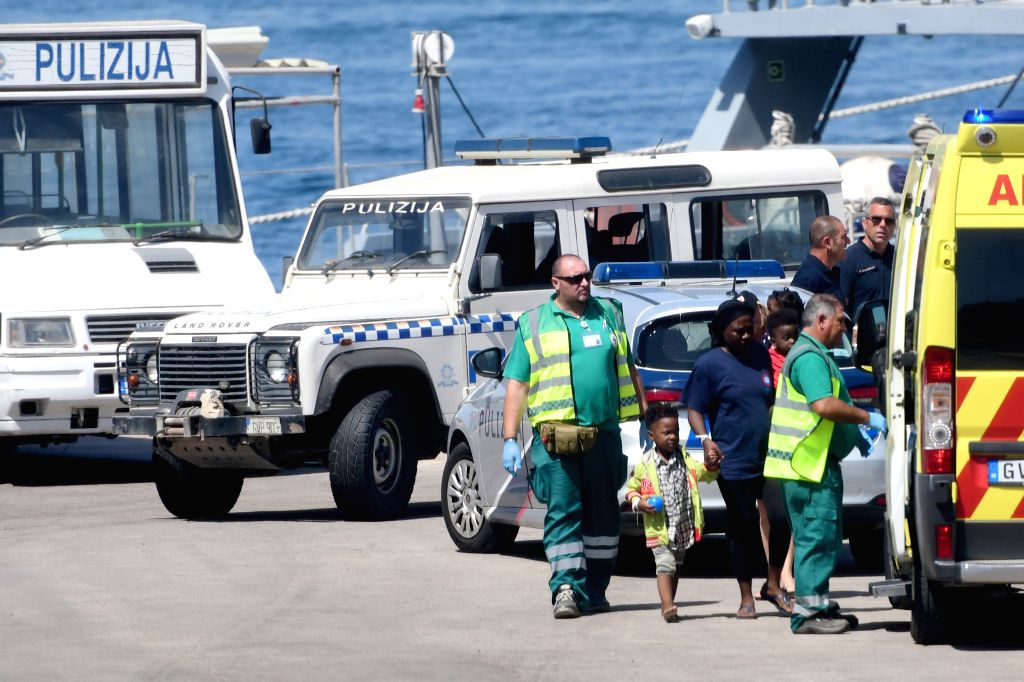 FLORIANA, Aug. 5, 2019 - A female migrant holds two child migrants to get on an ambulance in Floriana, Malta, on Aug. 4, 2019. Forty migrants aboard the German-flagged NGO vessel Alan Kurdi were ...