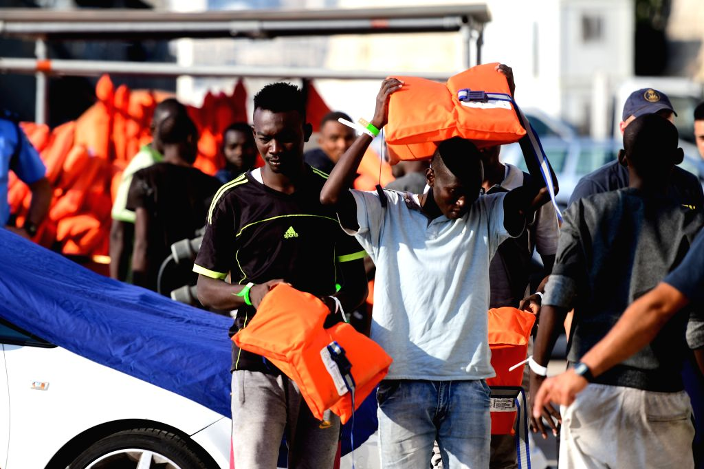 FLORIANA (MALTA), July 25, 2019 Migrants take off life jackets when they disembark at a naval base in Floriana, Malta, on July 25, 2019. A group of 76 migrants have been rescued by the ...
